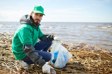 Young volunteer looking at camera and putting rubbish to plastic bag while sitting on shore