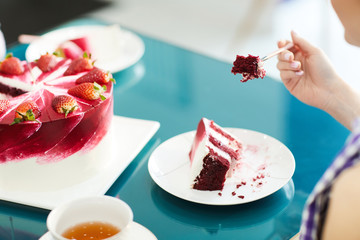 Crop unrecognizable woman eating Red Velvet cake with cup of tea in cafe