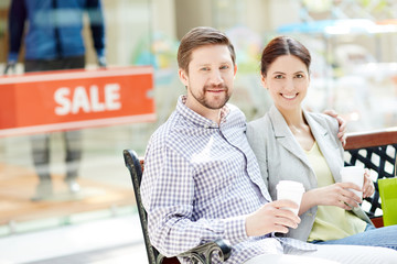 Beautiful content man and woman sitting on bench in shopping center having coffee in cups and smiling at camera