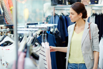 Beautiful young female in casual outfit looking at clothes on rail while standing in nice store