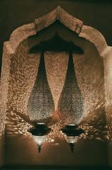 Moroccan bronze lanterns with traditional ornament in Arabic style. Night illumination in Marrakech, Morocco.