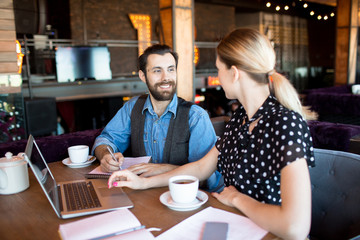 Trendy woman and man sitting with laptop and teacups at table chatting and working in relaxation