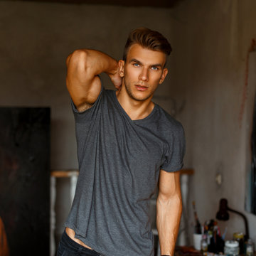 Fresh portrait of a beautiful model man in a gray T-shirt in the studio