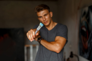 Young handsome artist man in a gray T-shirt with a brush in his hands in the studio. Art