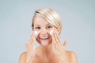 Happy woman with foam for washing on her face. Perfect clean skin.