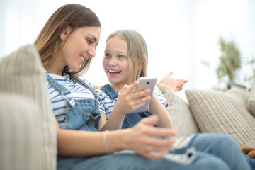 close up.happy mom and her daughter are watching videos on smartphone