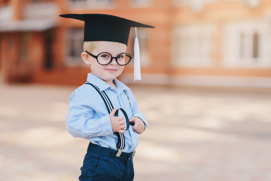 Little smart boy in spectacles, academic hat and glasses standing in the backyard of the school. Holds a magnifying glass in his hands
