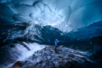 A hiker photographs the opening of a moulin (a tunnel though the glacier) in the ceiling of a glacial cave under the Mendenhall Glacier.