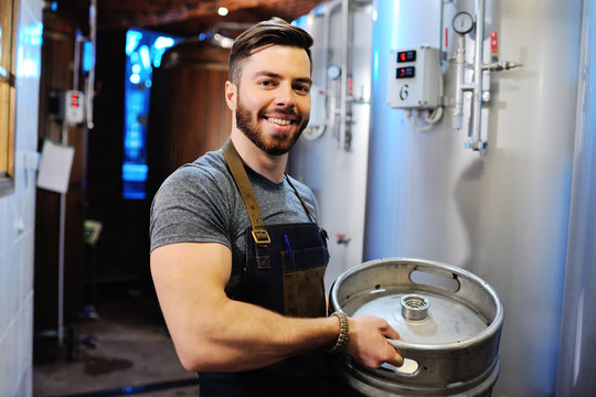 Male brewer with a metal beer barrel on the background of the brewery