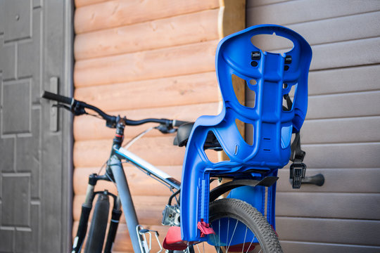 Bike with children carrying  seat attached. Cycle with kids transportation equipment stand near wooden garage. Family safety sport activity concept
