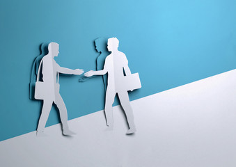 Folded Paper art origami. Two Businessman shaking hands on a business deal opportunity.Paper craft...