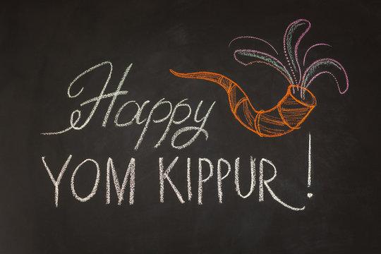 Inscription Happy Yom Kippur and symbol Rosh Hashanah on chalkboard background.