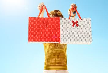 modern woman hiding behind shopping bags against blue sky
