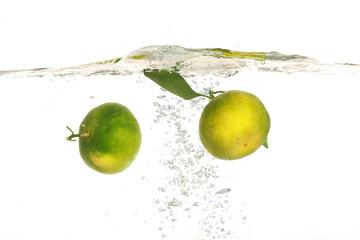 Green citrus or tangerine drop in water