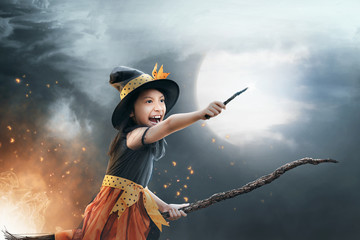 Funny asian child girl flying on the broomstick