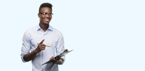 Young african american man holding a clipboarad surprised with an idea or question pointing finger with happy face, number one