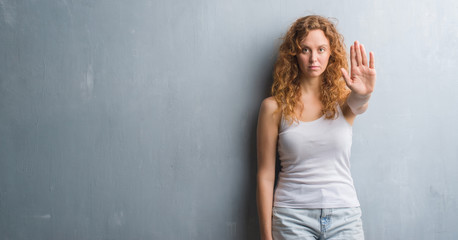 Young redhead woman over grey grunge wall with open hand doing stop sign with serious and confident expression, defense gesture