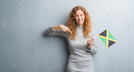 Young redhead woman over grey grunge wall holding flag of Jamaica with surprise face pointing finger to himself