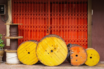 Old stock of yellow wooden beams roll nylon rope on floor outside shop building for sale.
