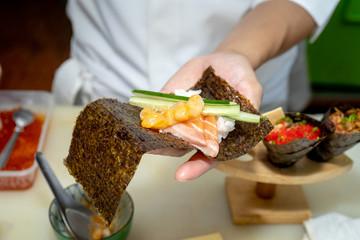 Japanese chef making sushi at restaurant.
