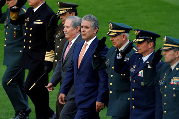 Colombia's President Ivan Duque and Defense Minister Guillermo Botero march with military heads during Botero's inauguration ceremony at the Jose Maria Cordova military school in Bogota, Colombia