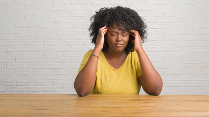 Young african american woman sitting on the table at home with hand on head for pain in head because stress. Suffering migraine.