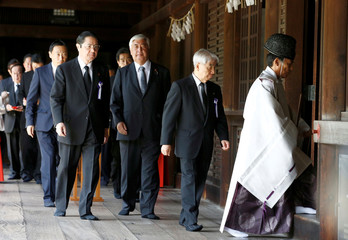 A Shinto priest accompanies Japanese lawmakers as they visit the Yasukuni shrine to pay respects to the country's war dead in Tokyo