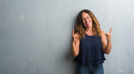 Middle age hispanic woman standing over grey grunge wall shouting with crazy expression doing rock symbol with hands up. Music star. Heavy concept.