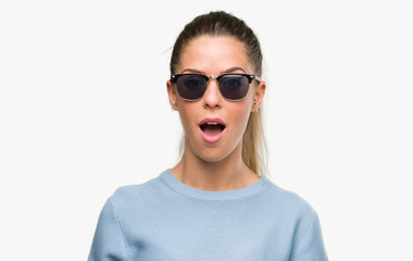 Beautiful young woman wearing sunglasses and ponytail scared in shock with a surprise face, afraid and excited with fear expression