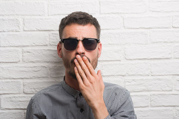 Young adult man wearing sunglasses standing over white brick wall cover mouth with hand shocked with shame for mistake, expression of fear, scared in silence, secret concept