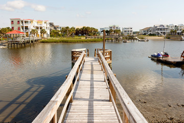 Long wooden dock into the inter coastal waterway in North Carolina, with luxury vacation homes and personal water craft