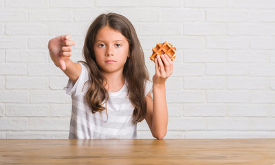 Young hispanic kid sitting on the table eating waffle with angry face, negative sign showing dislike with thumbs down, rejection concept