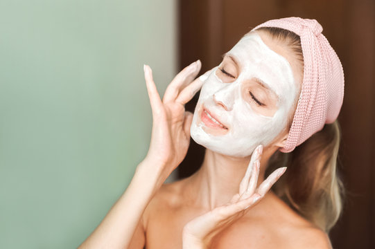 Beauty Treatments. Young woman is applying a mask, cream on her face close-up. Facial skin care portrait of a beautiful girl with a towel on her head applying facial mask