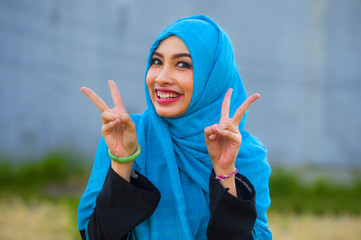 young beautiful and happy Asian woman in hijab muslim head scarf posing to the camera playful having fun doing success victory V sign with fingers