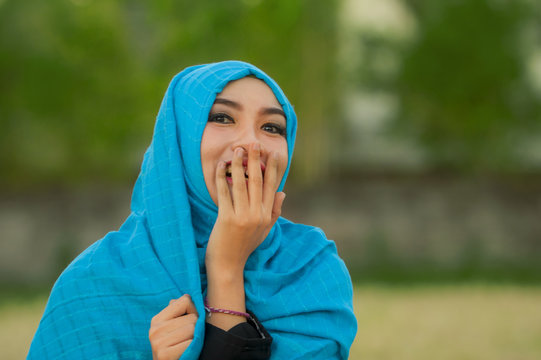 lifestyle isolated portrait of young beautiful and happy Asian woman in hijab muslim head scarf laughing shy and playful having fun and smiling cheerful