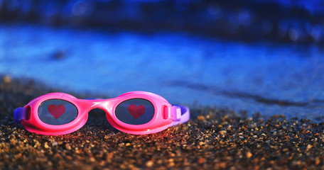 Pink swimming glasses on the sand with the red hearts on the lens. Diving or swimming equipment of the kids. Conceptual picture of the summer vacation, kids drowning or end of the recreation season.