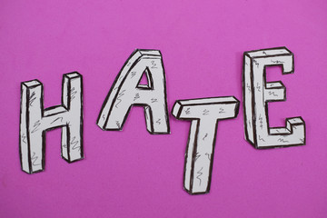 written word hate, white on a pink background