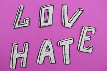 written words love and hate, white on a pink background