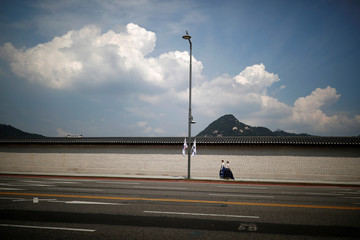 Women in traditional costume Hanbok walk along the wall of Gyeongbok Palace on a hot summer day in Seoul
