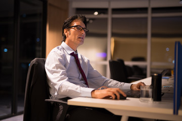 Mature Businessman Working And Thinking In Office At Night