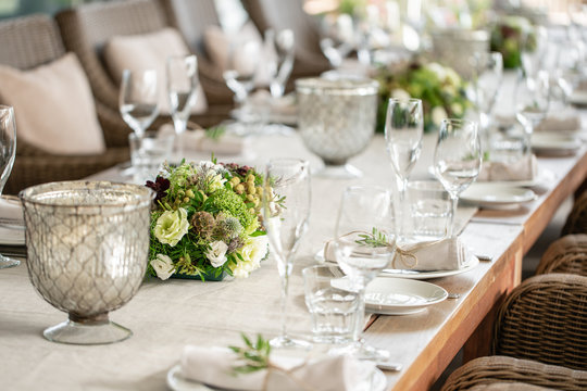 Wedding Banquet or gala dinner. The chairs and table for guests, served with cutlery and crockery. Covered with a linen tablecloth runner. party on terrace