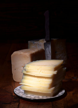 pieces of cheese in dark ambience on rustic wooden board