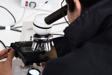 a scientist examines a bacterium in a microscope, seeks a cure for the disease