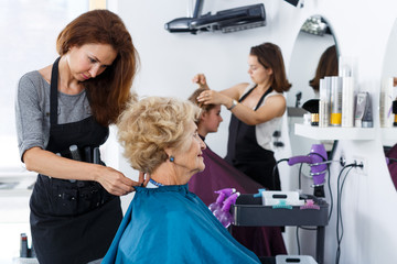 Stylist preparing customer for hair styling