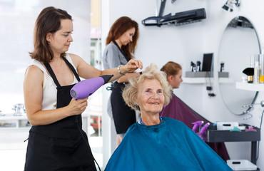 Stylist using hair dryer for senior woman
