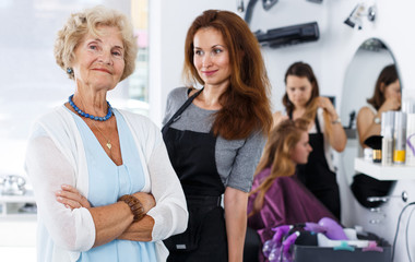 Smiling elderly woman with hairdresser