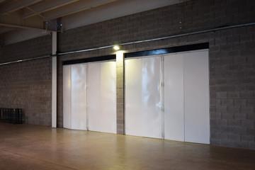 a huge iron white door in an empty hangar