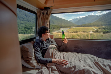 Young Asian man drinking beer and working with laptop computer on the bed in camper van with snow mountain scenic view through the window, digital nomad on road trip concept