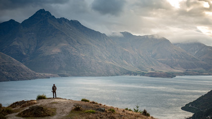 Young male photographer looking at mountain scenery during golden hour sunset on Queenstown hill in Queenstown, South Island, New Zealand. Travel and photography concept