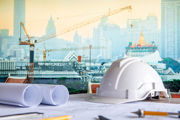 Architectural drawing plan with blueprint rolls, safety helmet and drawing tools on working table. Blurred crane and construction site in Bangkok in the background. Building construction concept